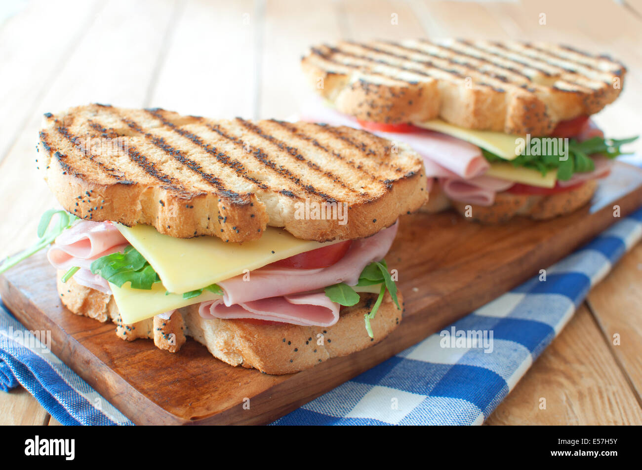 Grilled sandwiches with ham and cheese on top of a chopping board - Stock Image