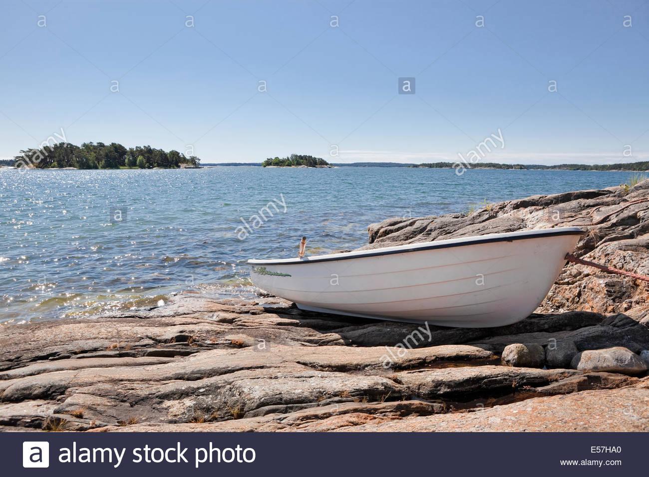 White rowboat on shore - Stock Image