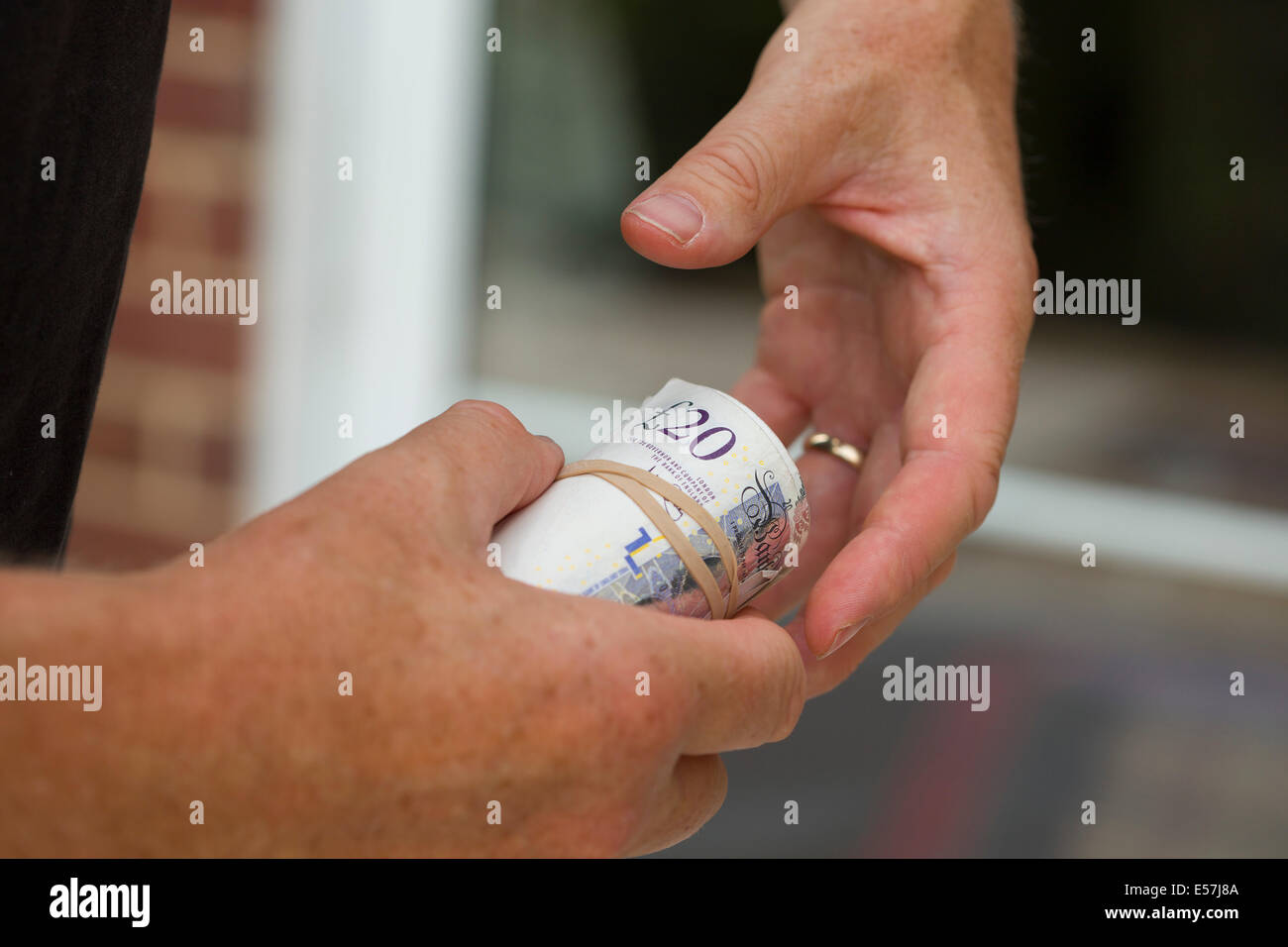 paying with cash, 2 hands and roll of money as if in payment maybe cash in hand. The cash is UK pounds sterling - Stock Image