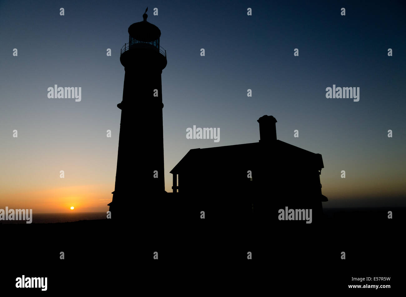 Lundy Island lighthouse sillouette at sunset - Stock Image