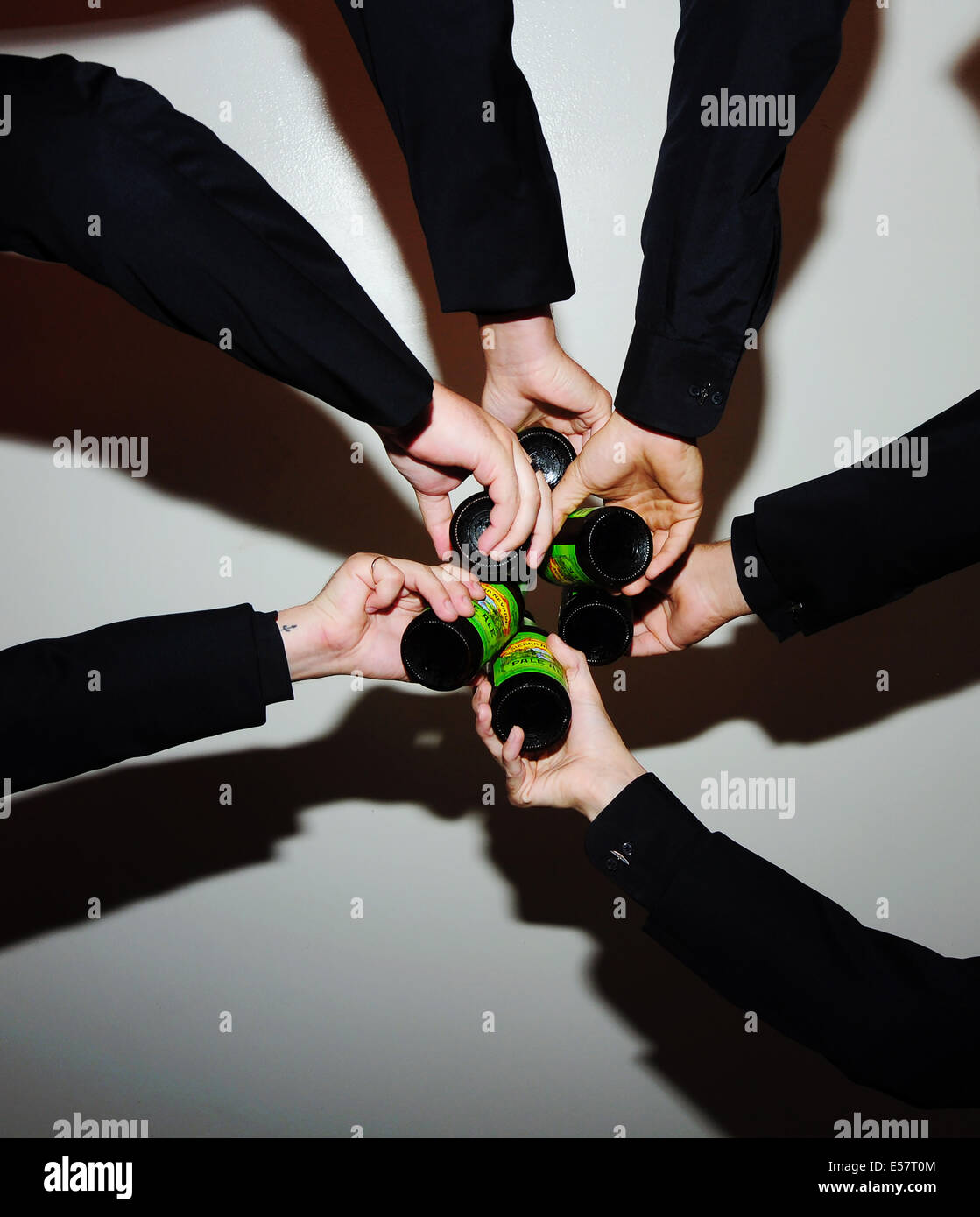 A group of men in suits toasting. - Stock Image