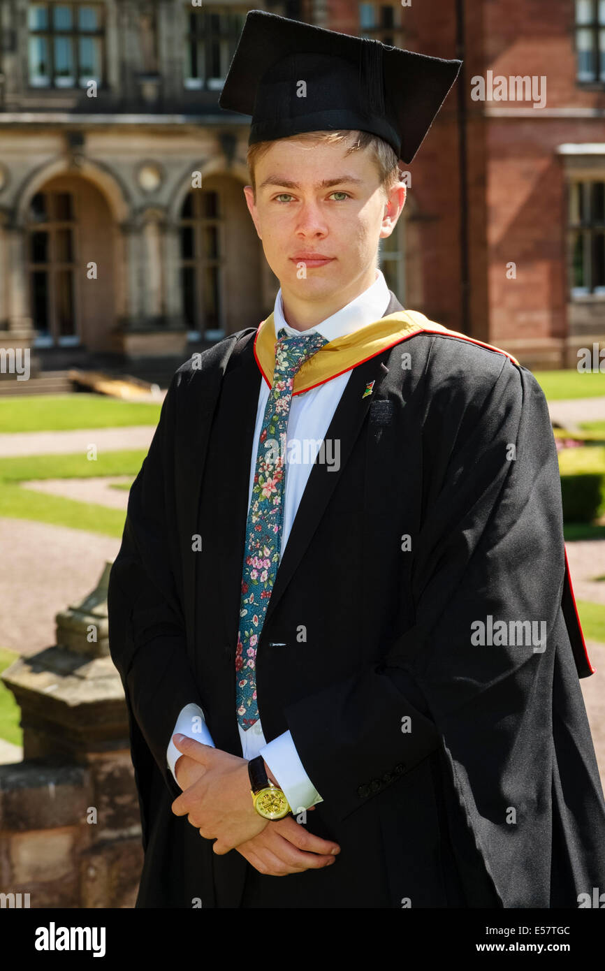 University student poses in traditional mortar board and gown on ...