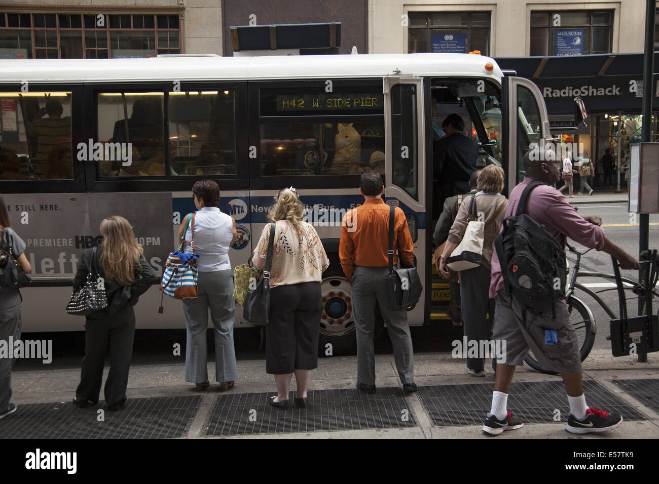 People waiting for a crosstown bus along 42nd Street in Manhattan, NYC. - Stock Image