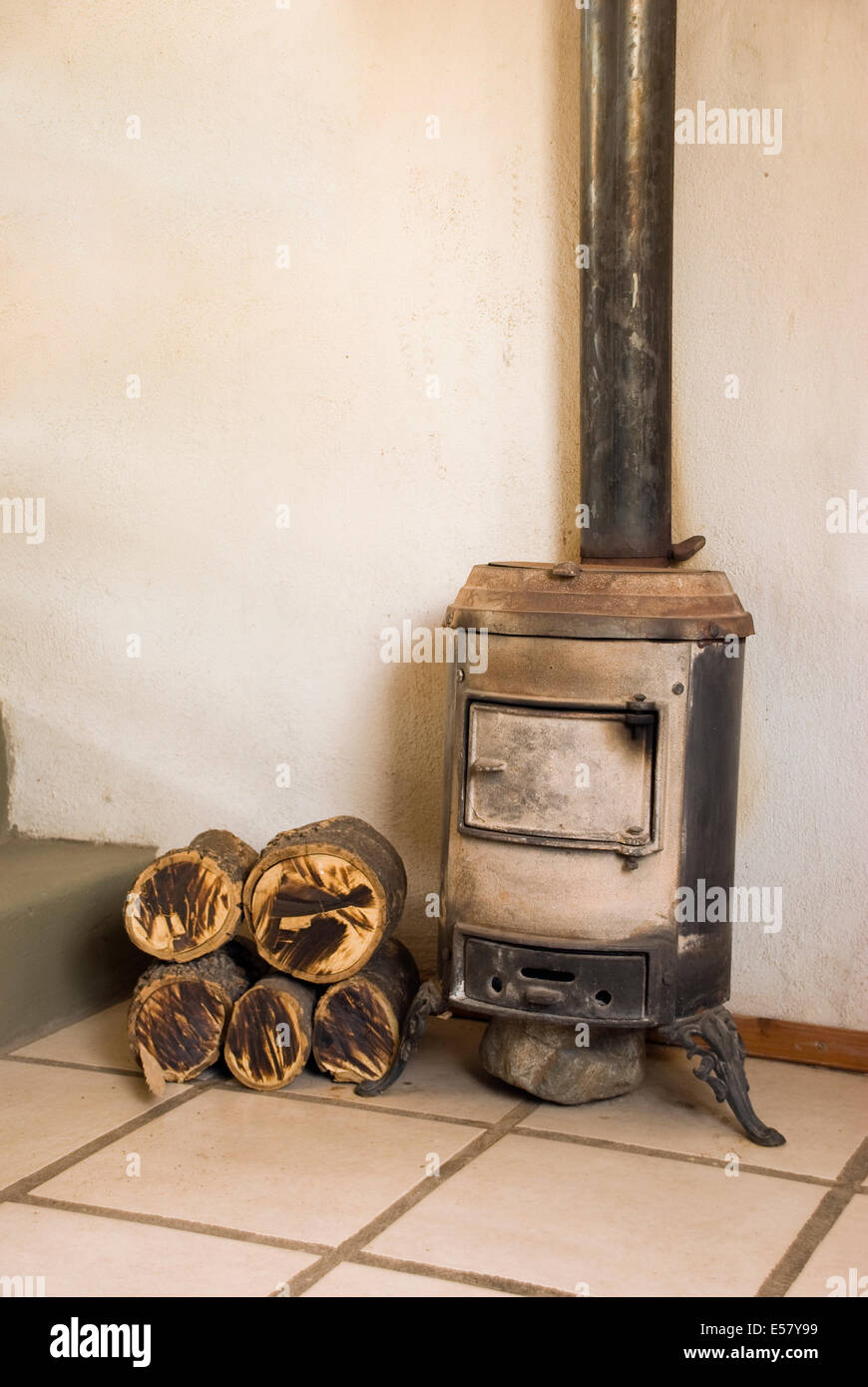 A salamander stove and some logs next to it - Stock Image
