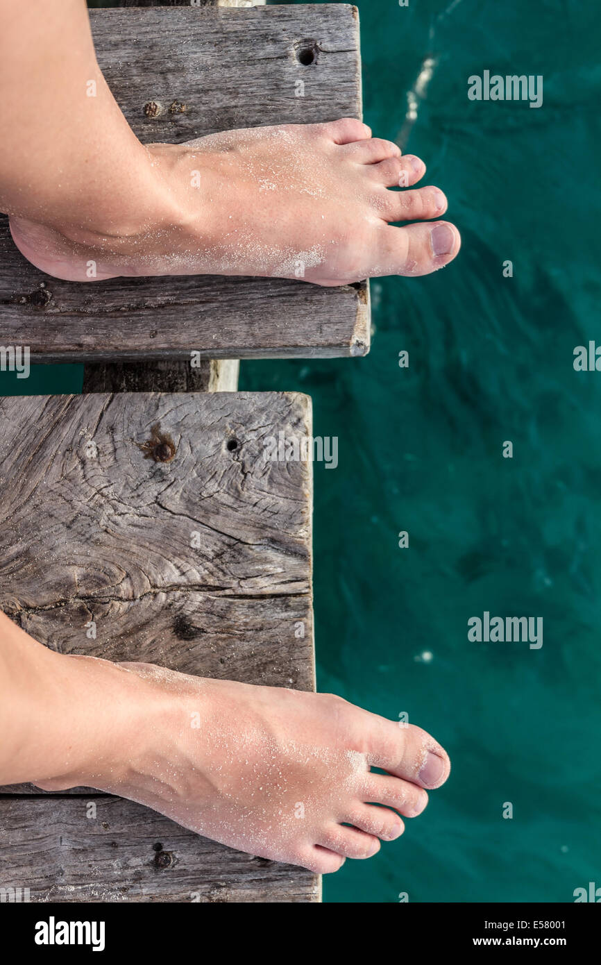 Women's bare feet standing by the edge of the dock - Stock Image