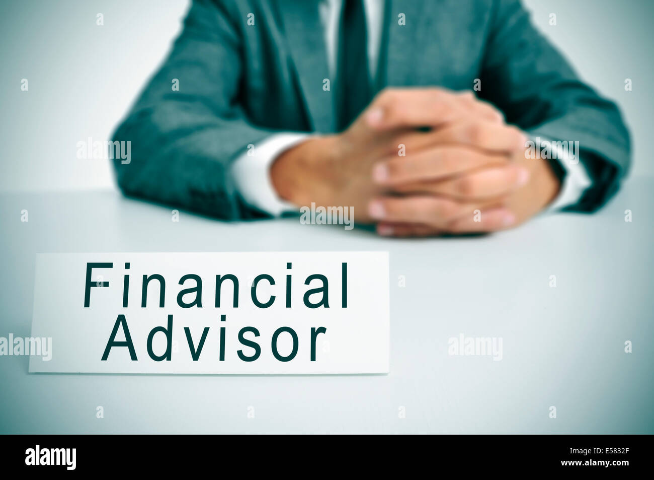 a man wearing a suit sitting in a desk with a signboard in front of him with the text financial advisor written - Stock Image