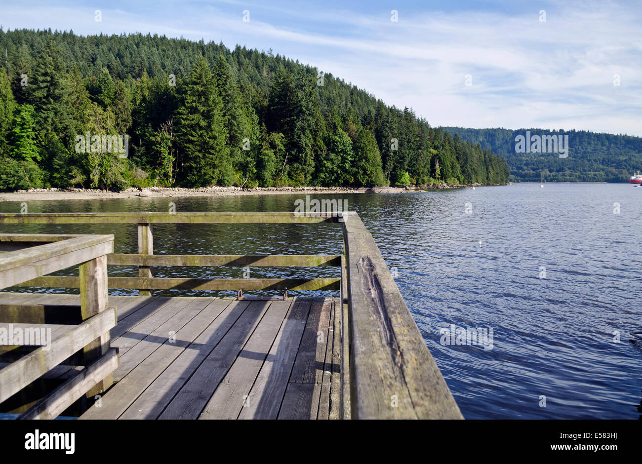 Wooden pier overlooking the waters of Burrard Inlet and forest of Belcarra Regional Park in Greater Vancouver. - Stock Image