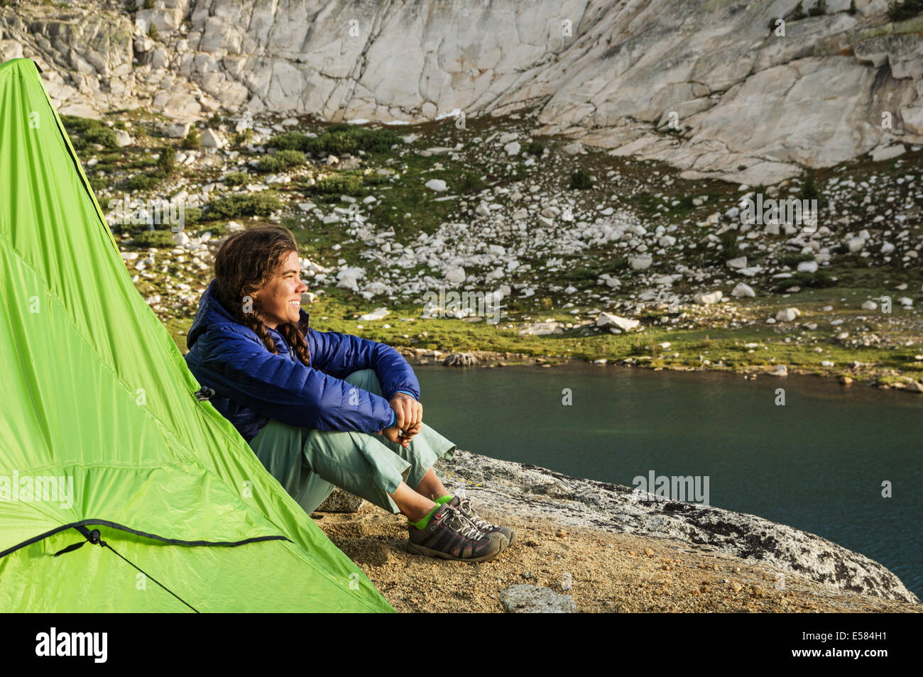 woman backpacking camper sitting next to her tent watching the sunset by Evolution Lake - Stock Image