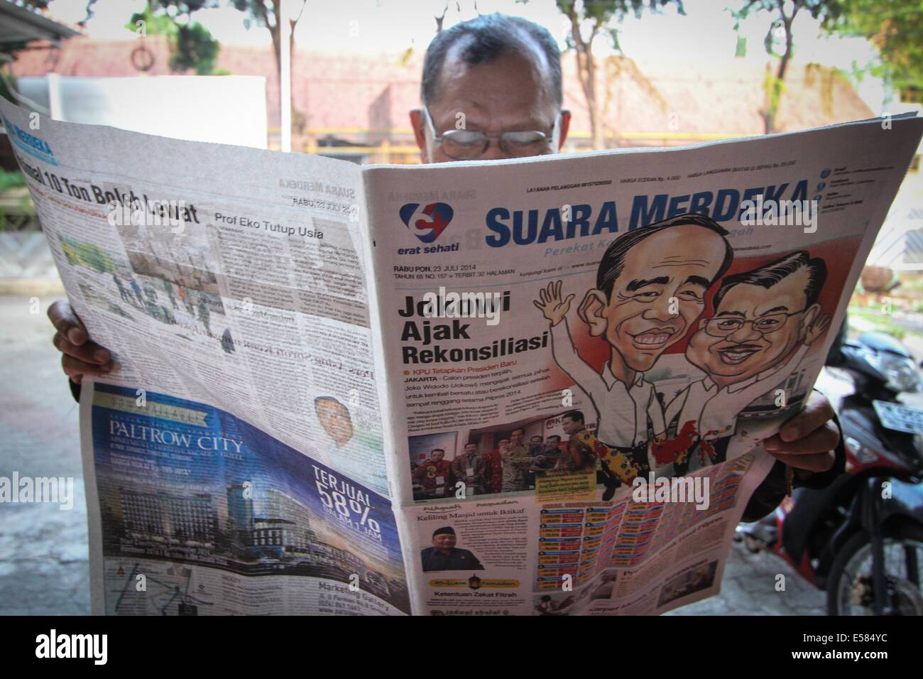 Semarang, Central Java, Indonesia. 23rd July, 2014.  A man reads a newspaper carrying the front page headline on - Stock Image