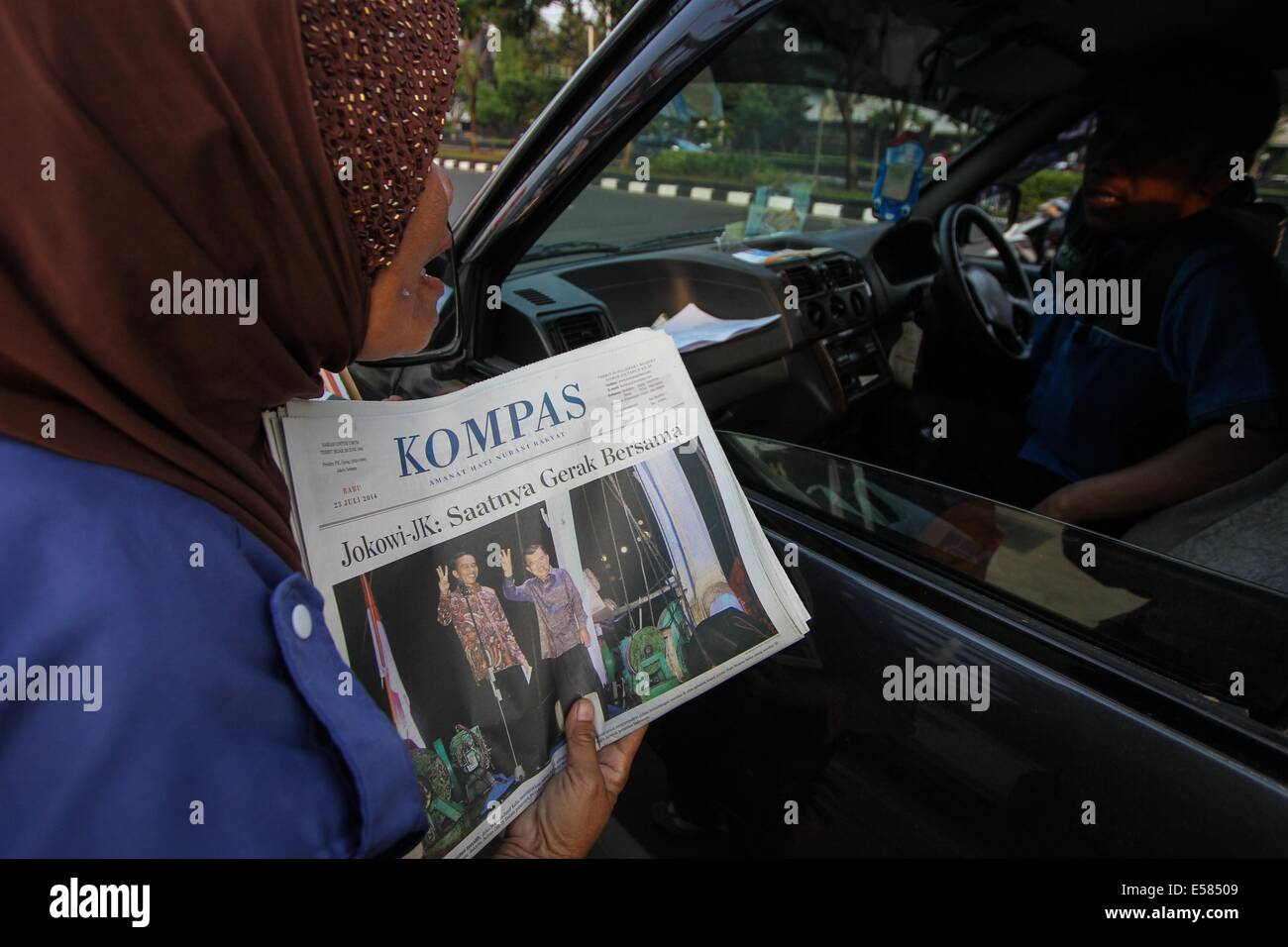 Semarang, Central Java, Indonesia. 23rd July, 2014.  A newspaper seller offers a newspaper carrying the front page - Stock Image