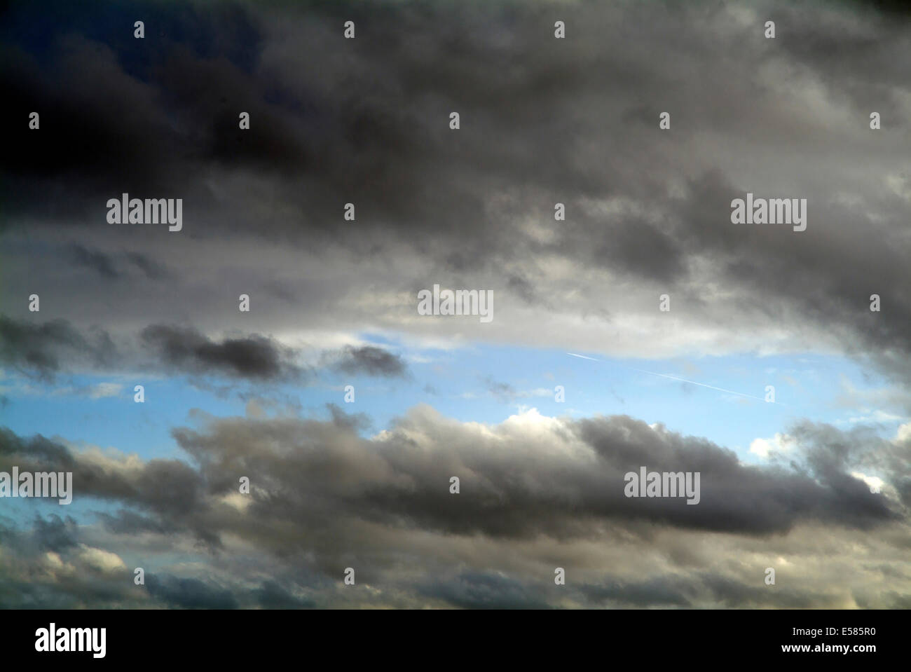 Grey rain clouds against blue sky - Europe Germany Berlin Stock Photo