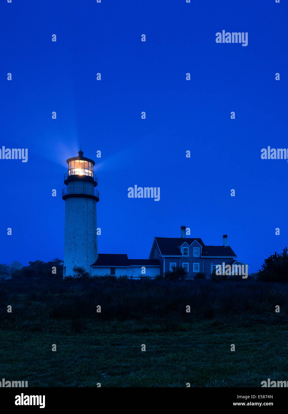 Lighthouse casts guiding light into dark blue night, - Stock Image