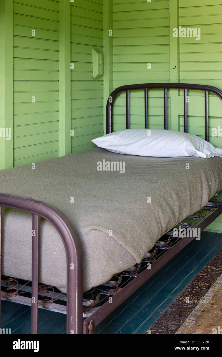 Simple bed in basic room. - Stock Image