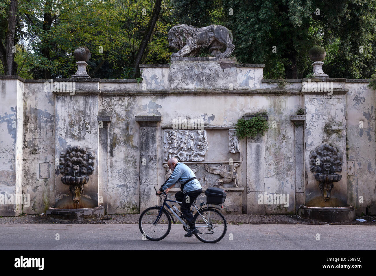 Man rides his bike past a rustic water fountain in the Villa Borghese, Rome, Italy - Stock Image