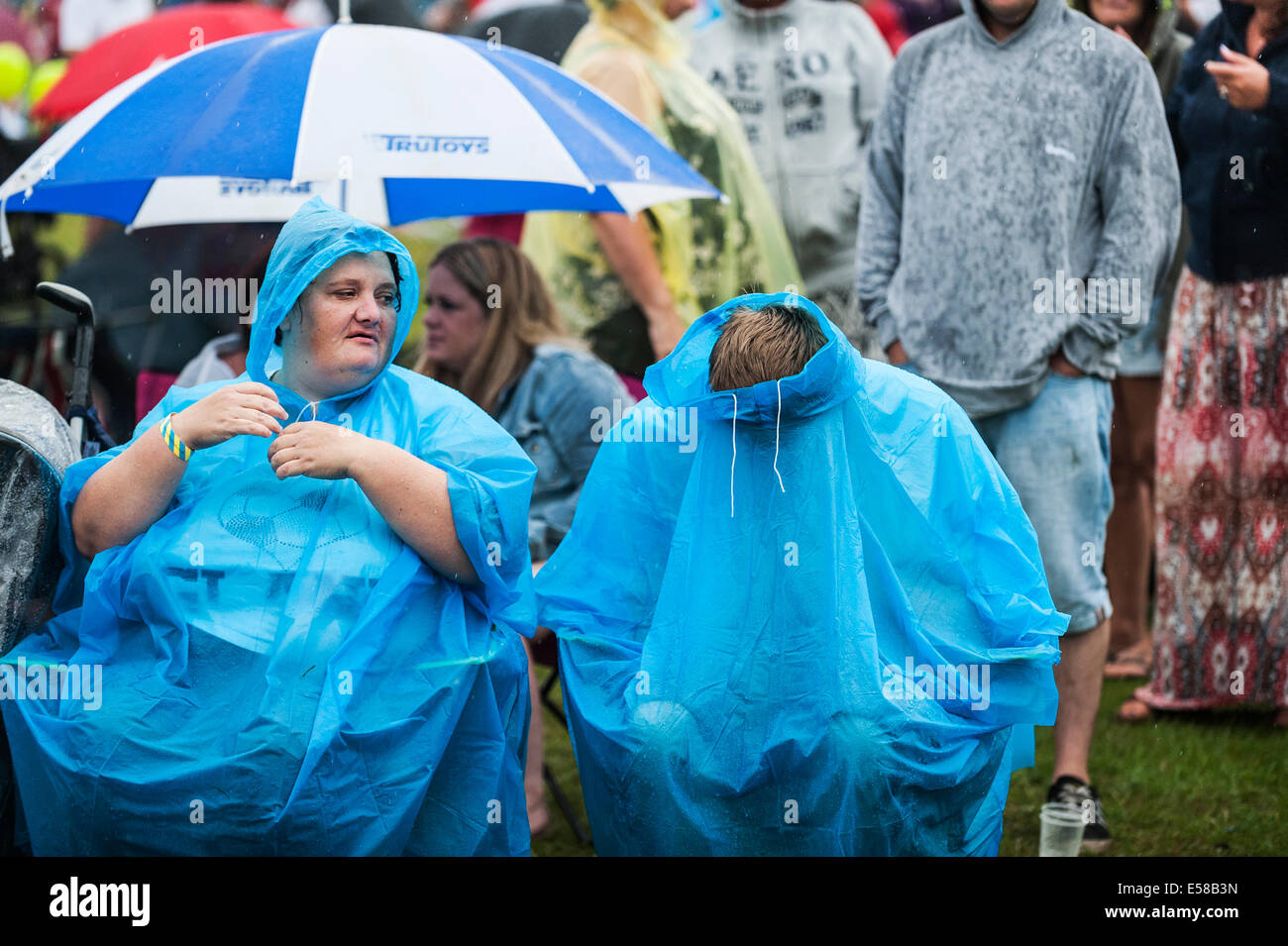 Festivalgoers sheltering from the bad weather at the Brentwood Festival. - Stock Image