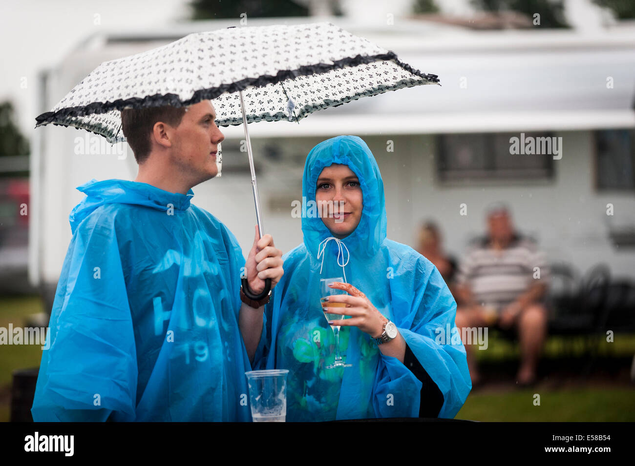 Festivalgoers enjoying themselves at the Brentwood Festival despite the bad weather. - Stock Image