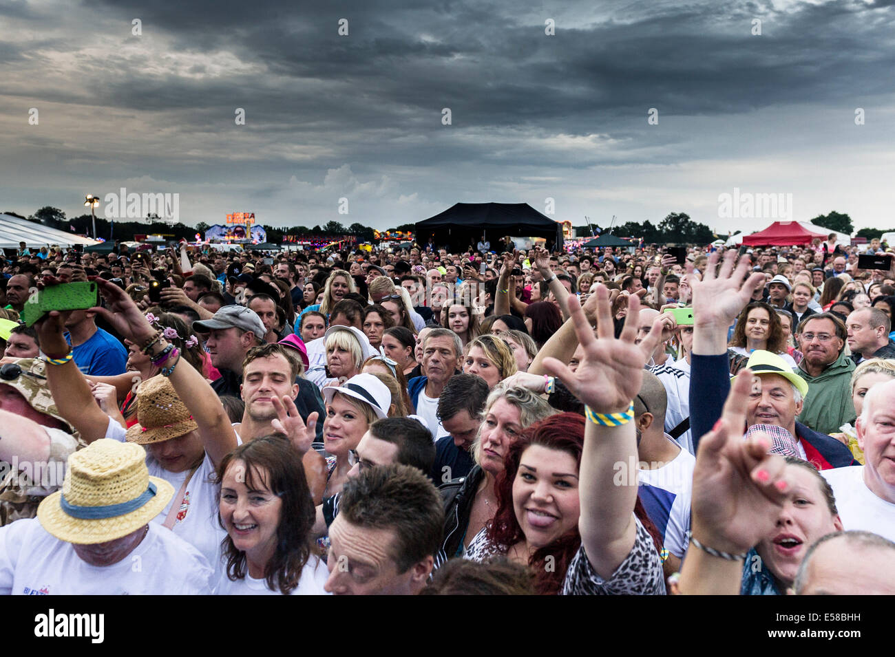 Festivalgoers at the Brentwood Festival enjoying themselves despite the bad weather. - Stock Image