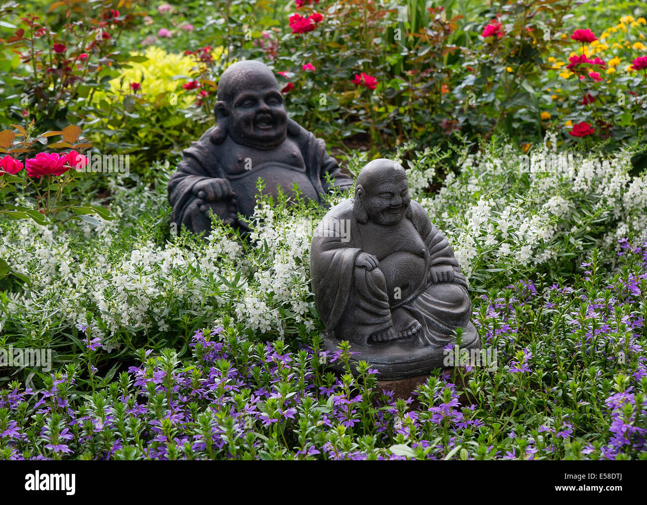 Home flower garden in full bloom with Buddha sculpture. - Stock Image