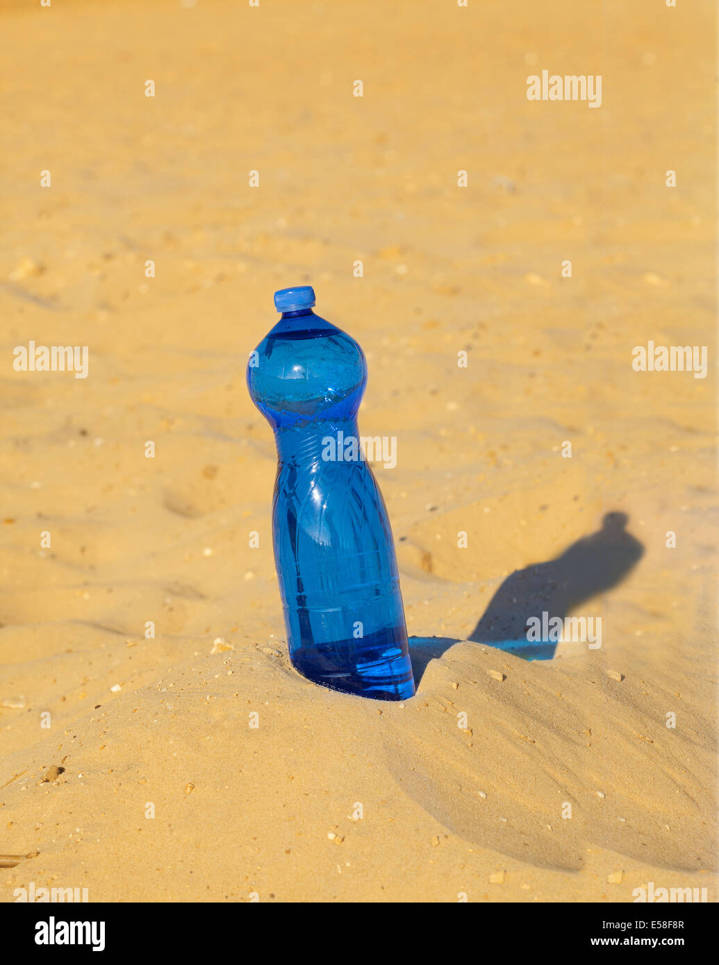 Bottle of water in the middle of the sandy desert - Stock Image