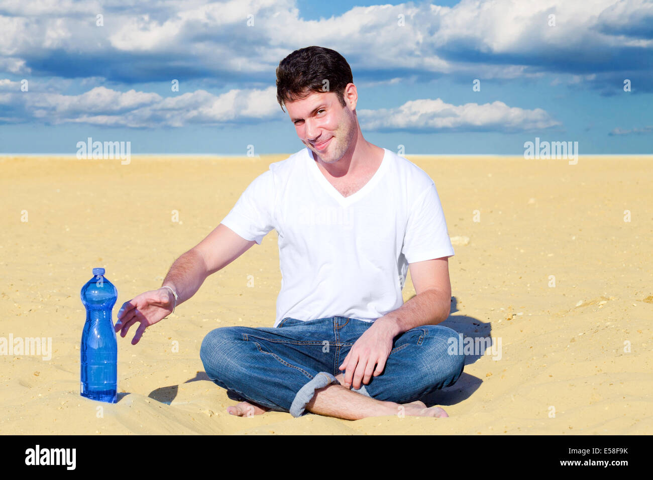 Handsome man reaching for a bottle of water in desert - Stock Image