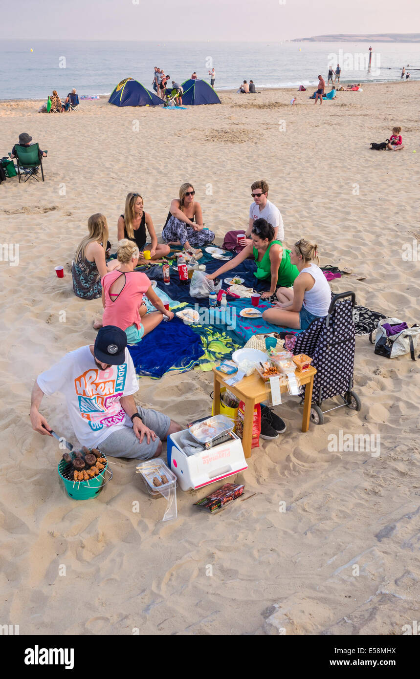 A barbecue on the Beach, on a warm evening, enjoyed by a group of young people at Bournemouth, Dorset, England, - Stock Image