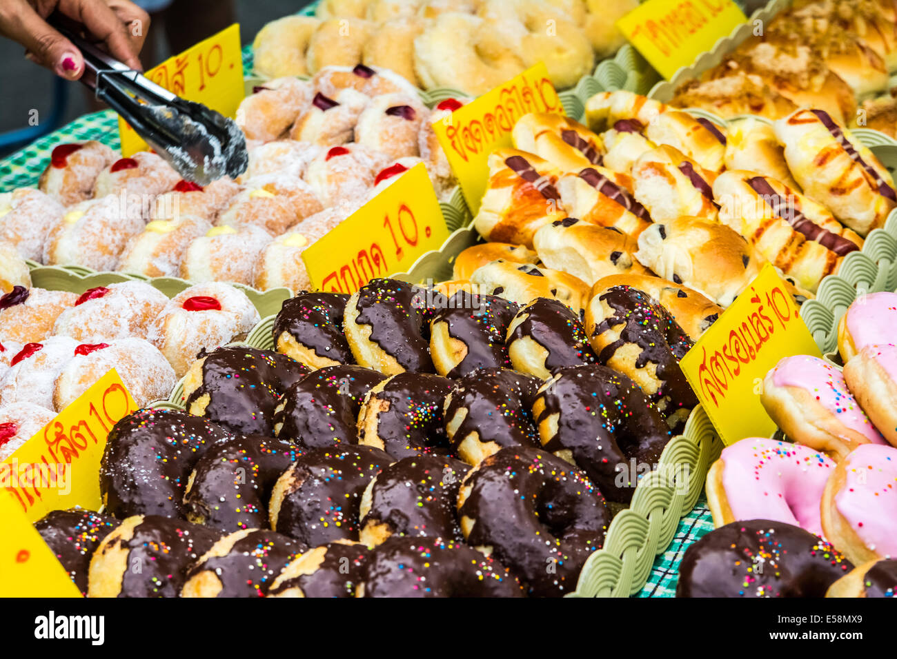 Glazed doughnuts, delicous desert in a nightmarket in Thailand. Ares a type of fried dough confectionery or dessert - Stock Image