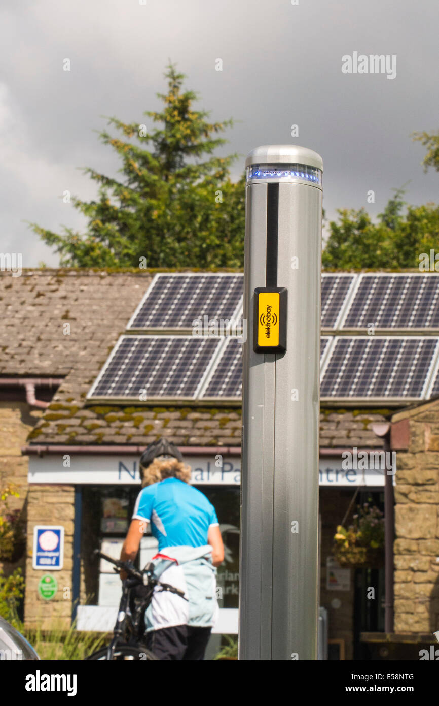 An electric vehicles charging station being charged by solar panels on a Northumberland National Park visitor Centre, - Stock Image