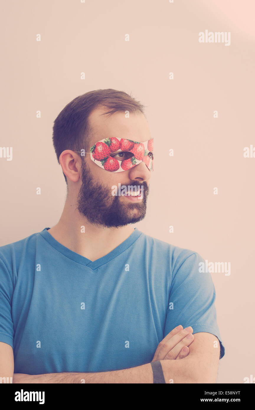 Superhero wearing mask with strawberries, daydreaming - Stock Image