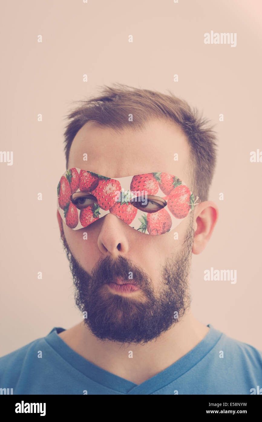Superhero wearing mask with strawberries, making silly faces. Retro colors - Stock Image
