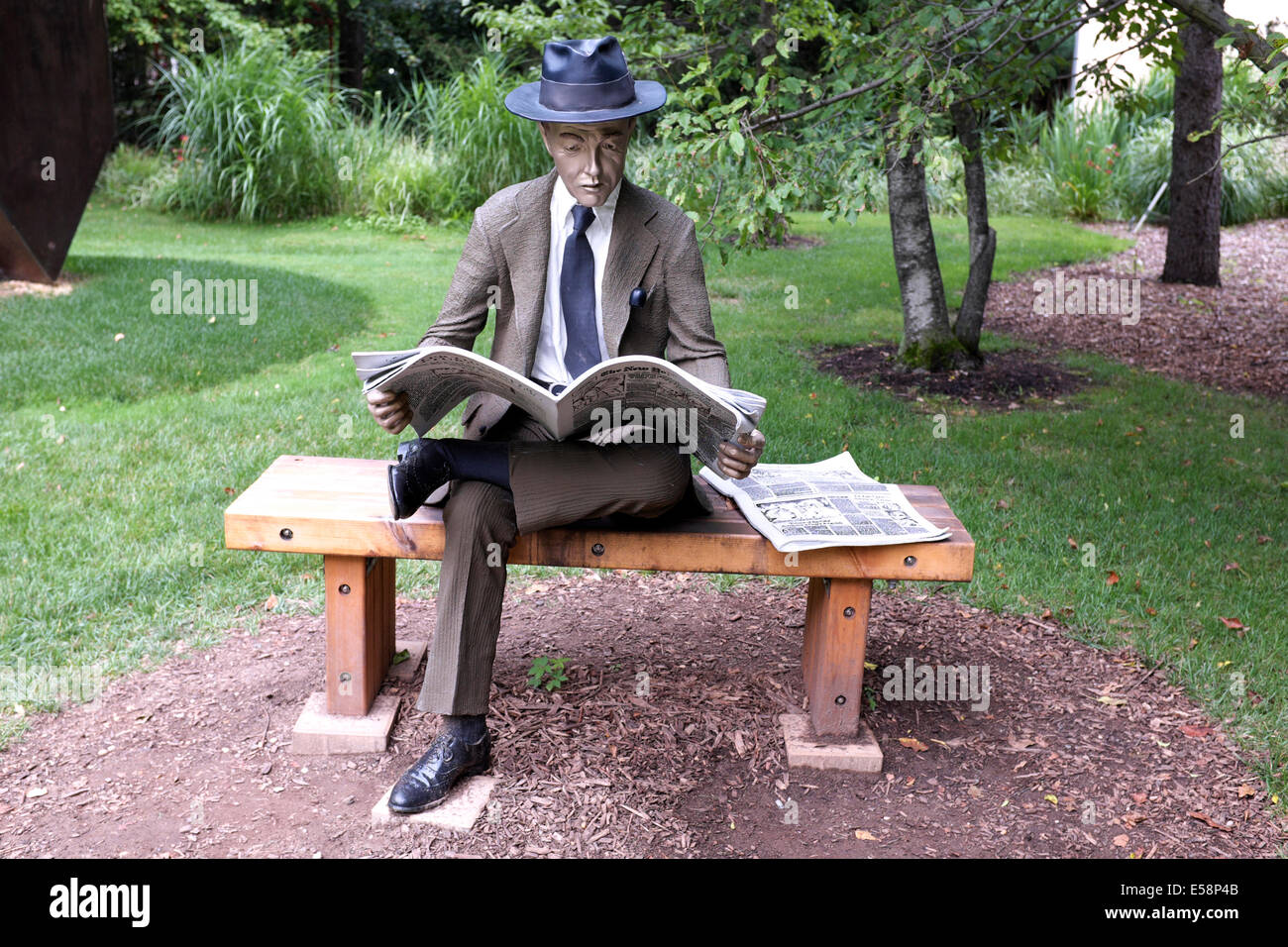 the newspaper reader - asian man reading newspaper on a bench stock