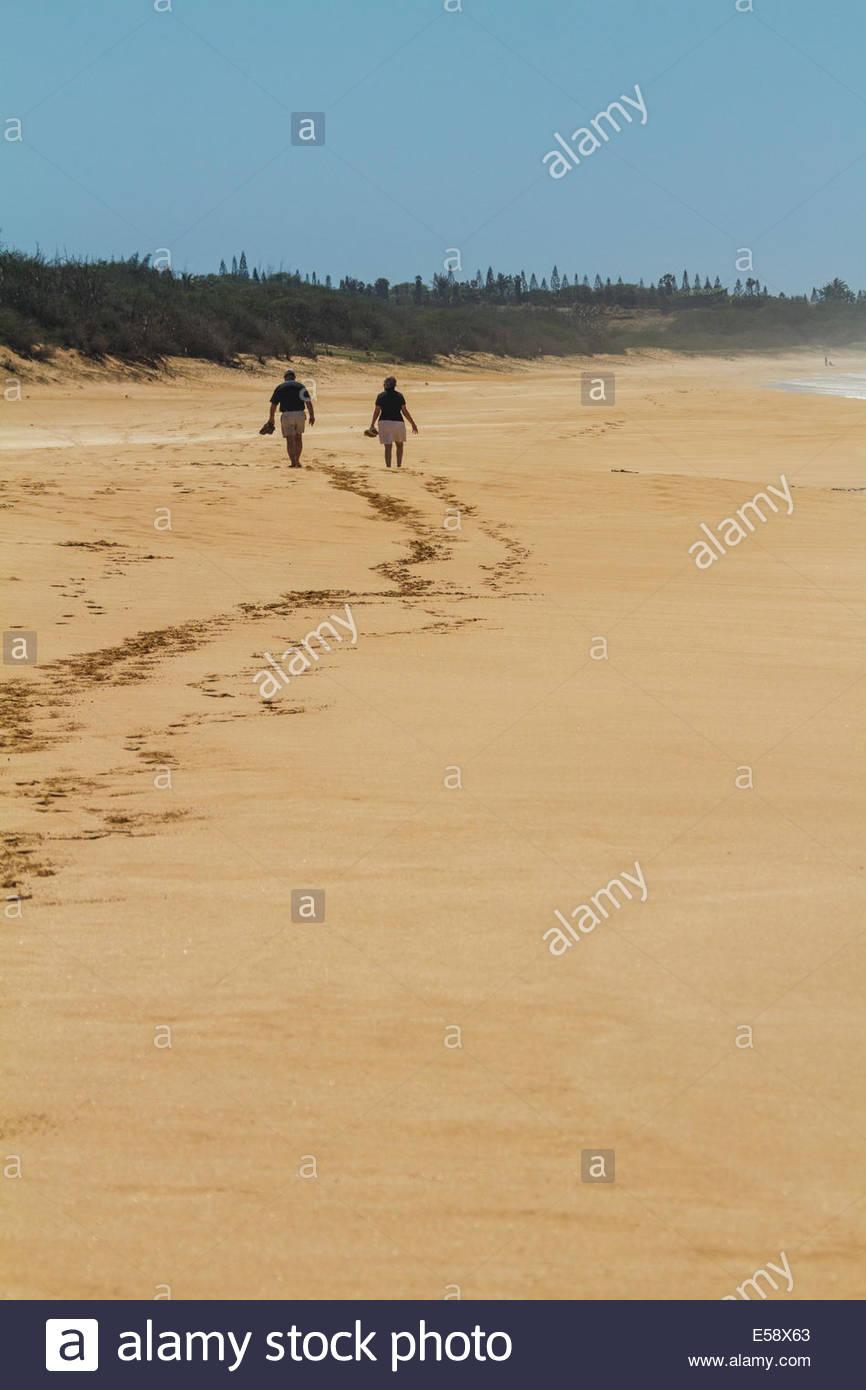 An older couple takes a romantic stroll along a deserted tropical beach on Molokai, Hawaii - Stock Image