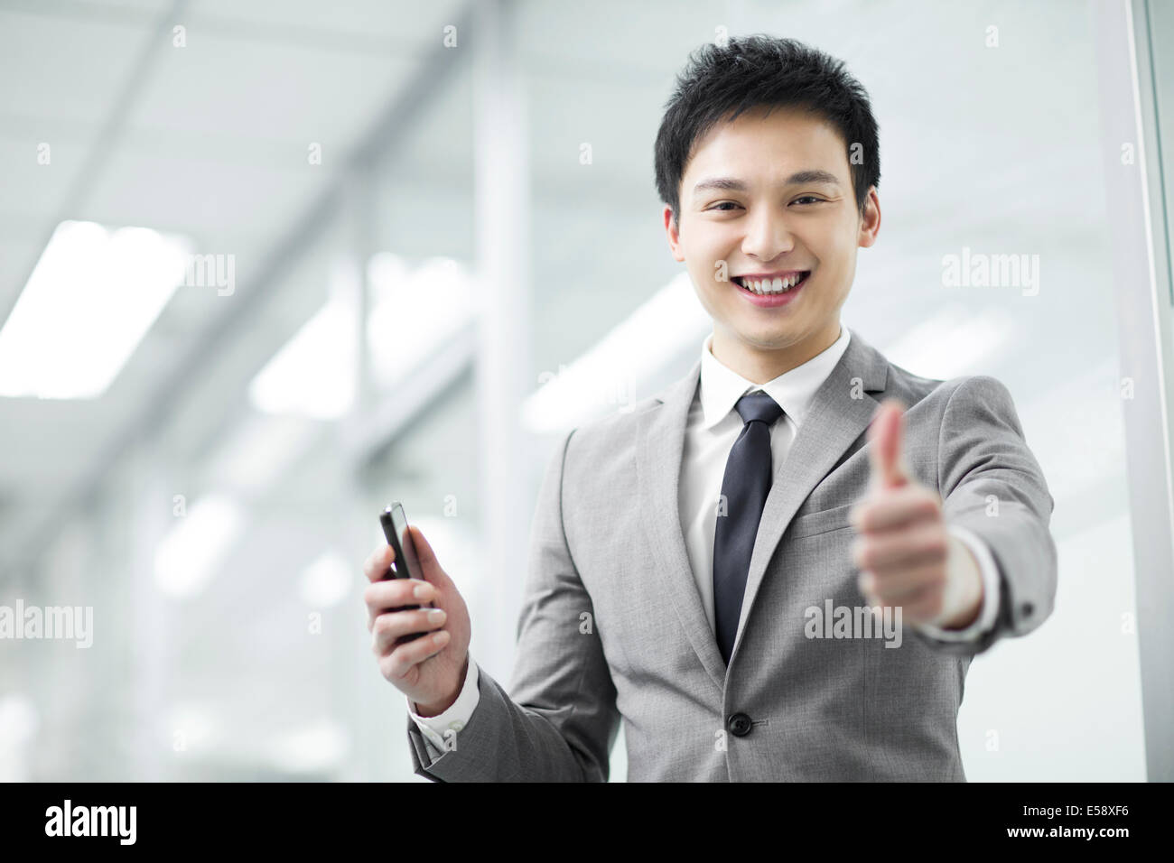 Young businessman giving thumbs up - Stock Image