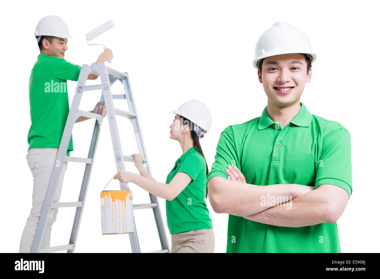 Happy volunteers painting the wall - Stock Image