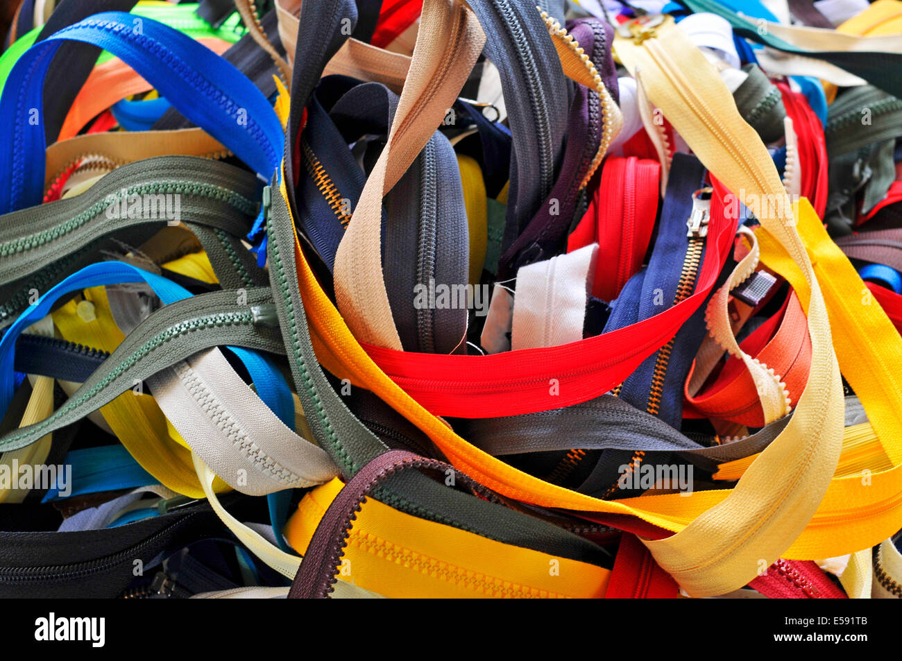 a pile of zippers of many sizes and colors - Stock Image