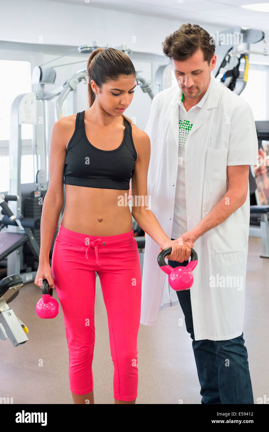 Male instructor guiding a woman in exercising Stock Photo