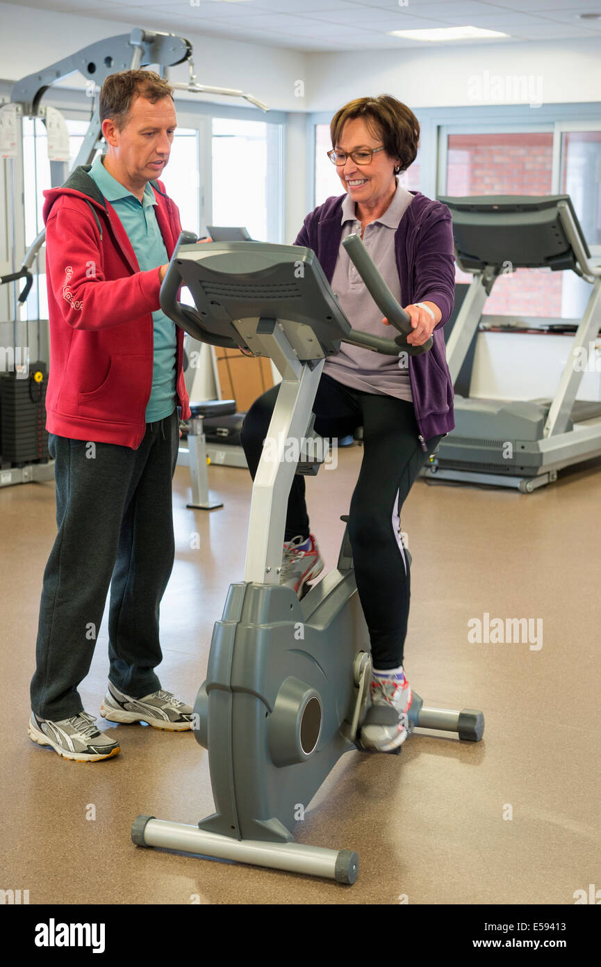 Trainer helping a woman with the cycle in a gym Stock Photo