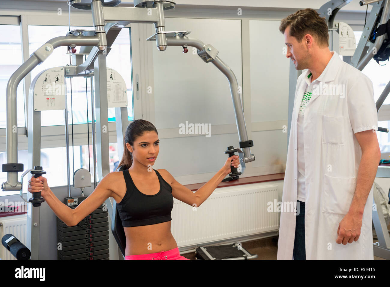 Male instructor guiding a woman in exercising - Stock Image