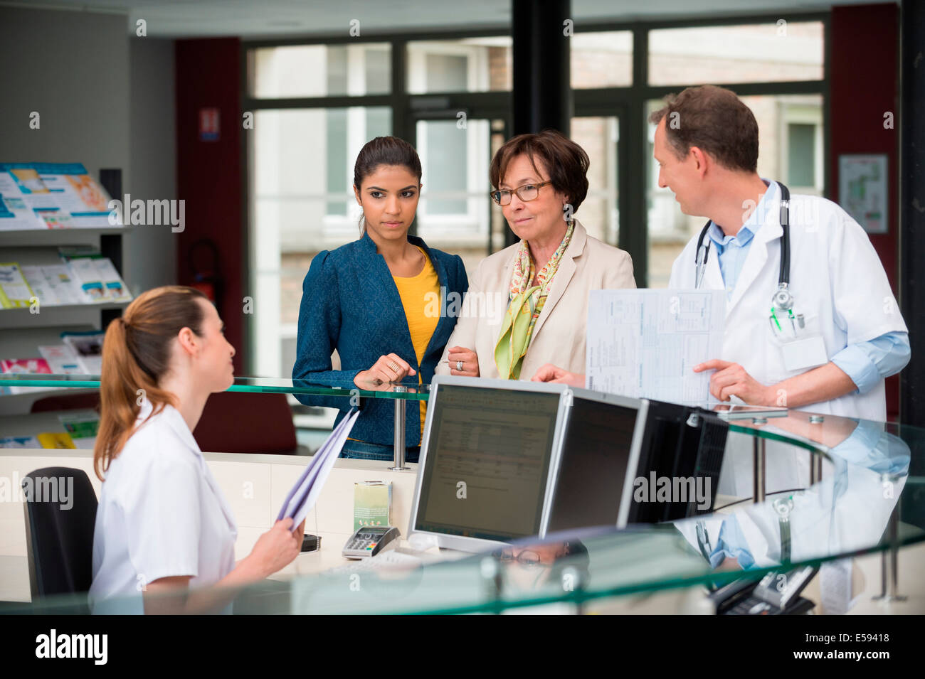 patients discussing with receptionist at hospital reception desk stock image