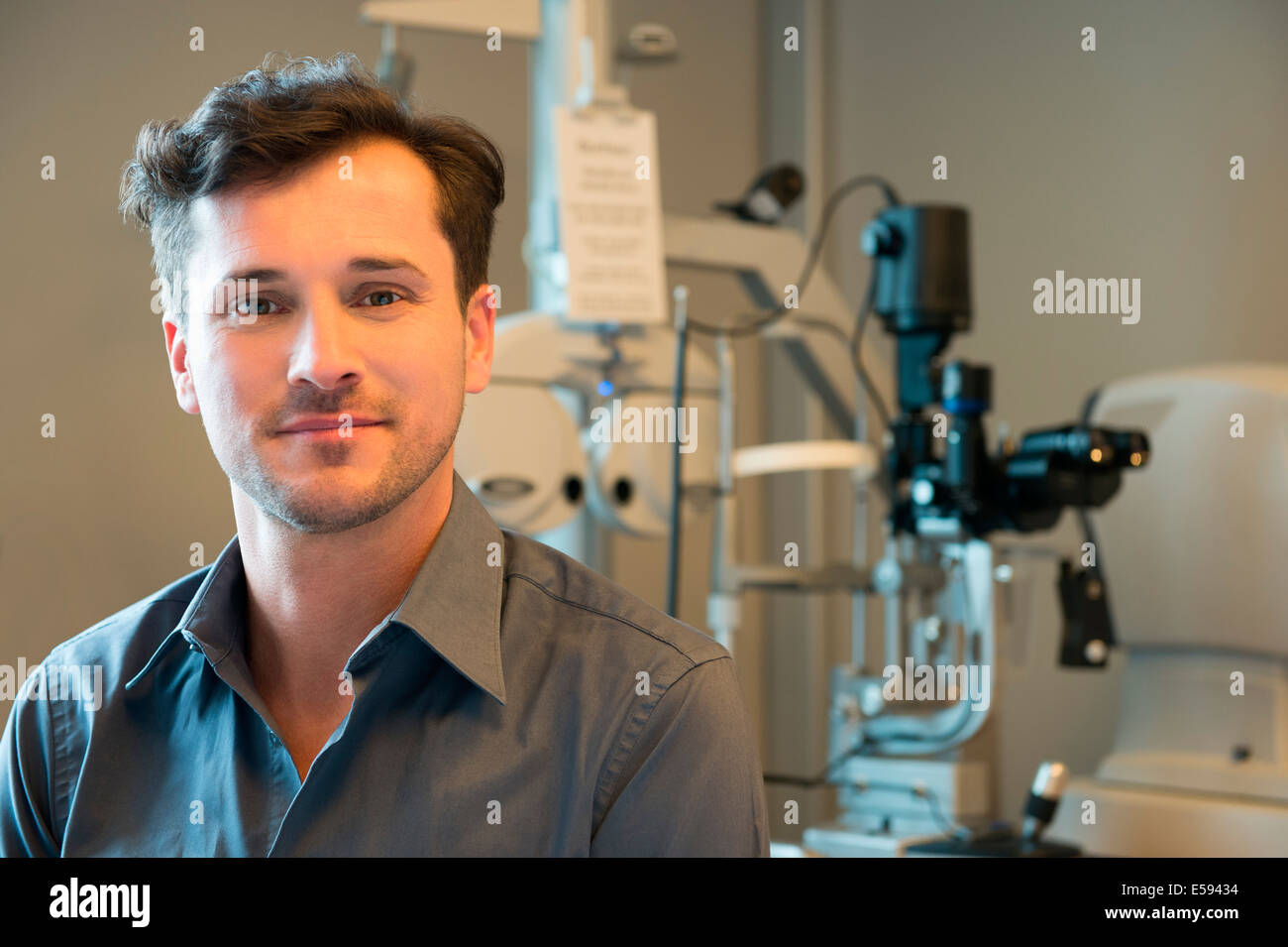 Male doctor with eye test equipment Stock Photo