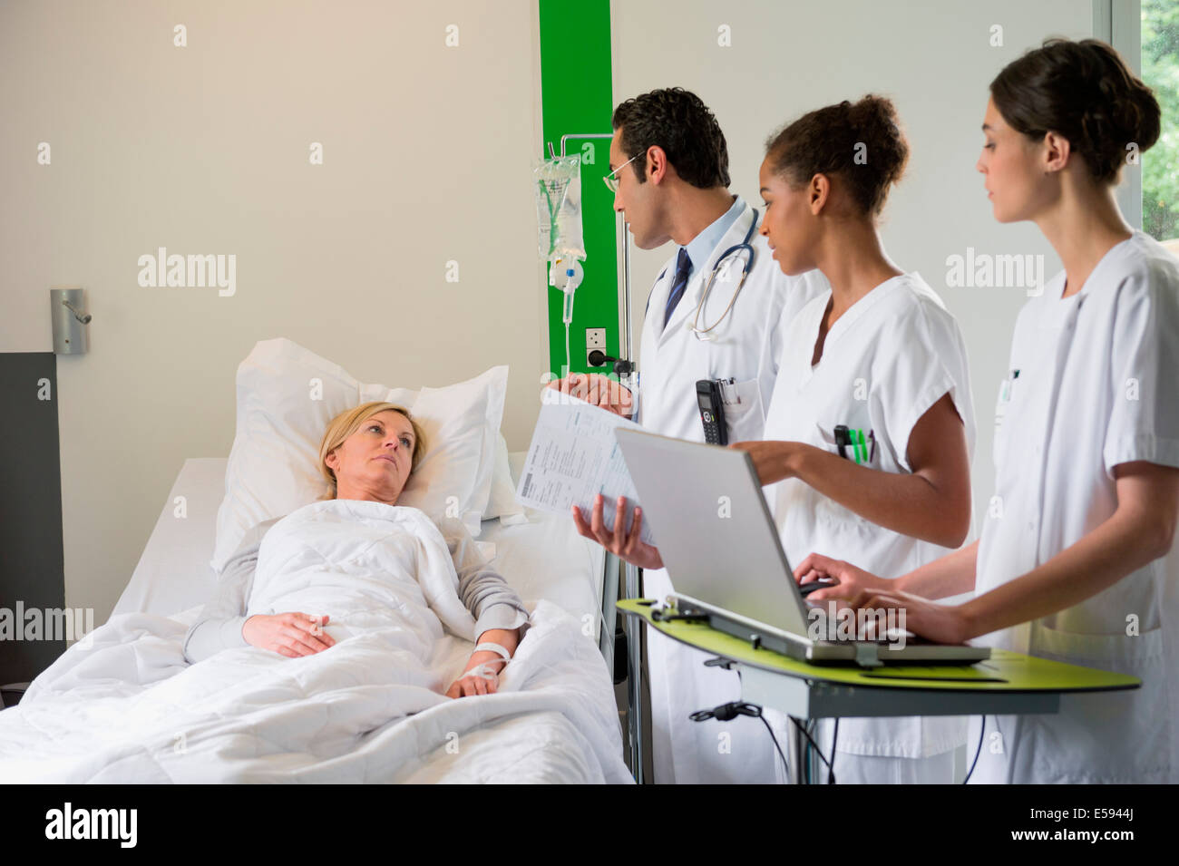 Medical team discussing female patient record in hospital bed - Stock Image