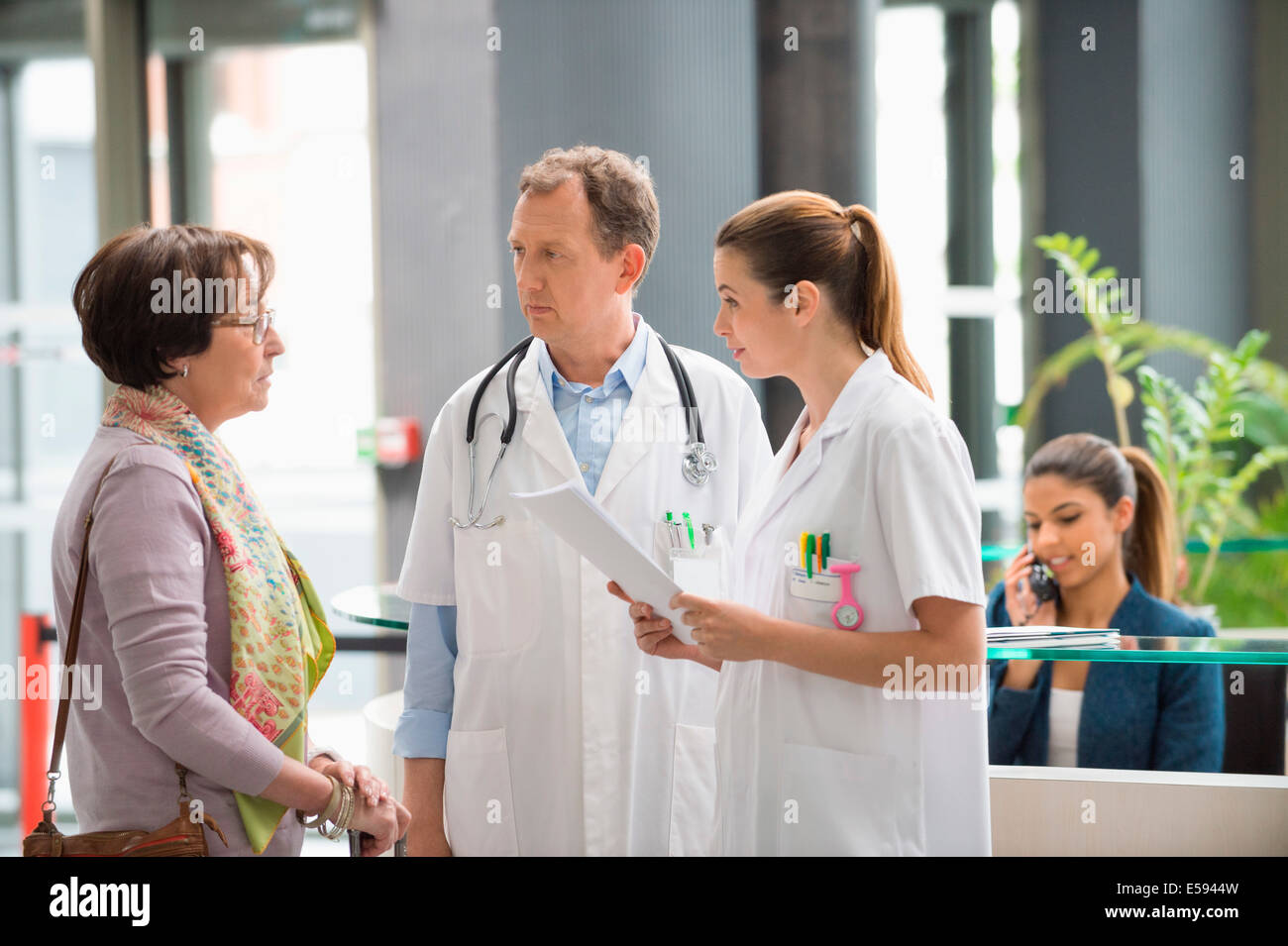 Doctors discussing with female patient at hospital reception desk - Stock Image