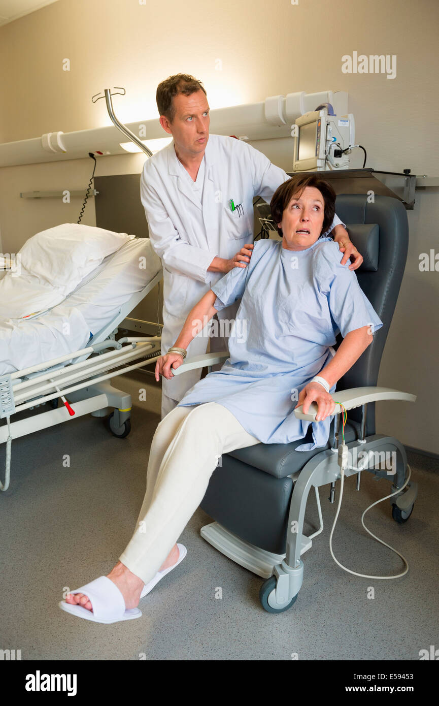 Male doctor helping female patient to sitting on chair in hospital - Stock Image