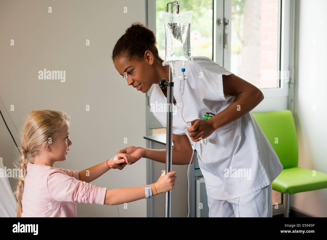 Female nurse helping to a girl patient to get up on hospital bed - Stock Image