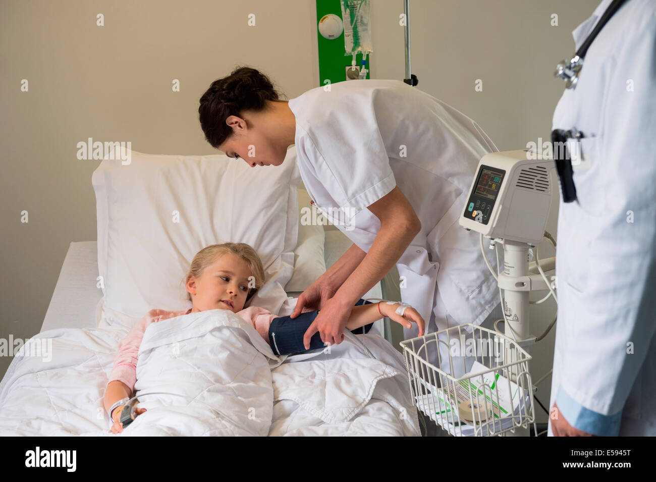 Medical attendants examining blood pressure of a girl patient in hospital bed - Stock Image