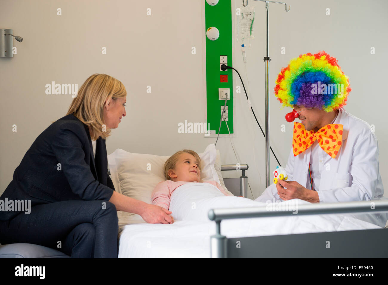Male doctor wearing clown costume making girl patient smile in hospital bed - Stock Image