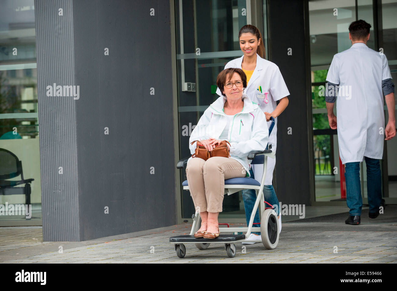 Female doctor pushing a patient sitting in a chair - Stock Image