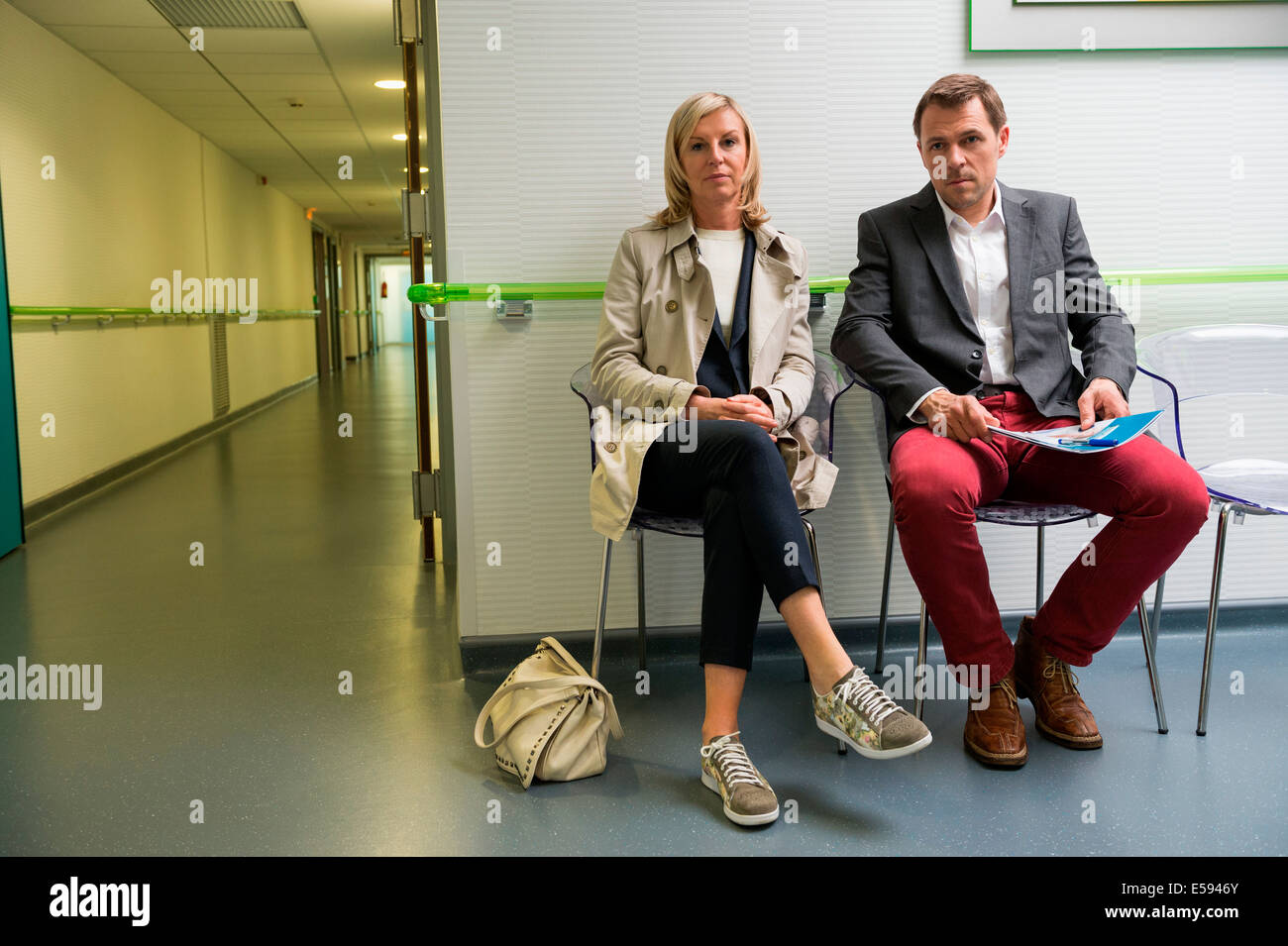 Couple sitting in the waiting area of a hospital - Stock Image