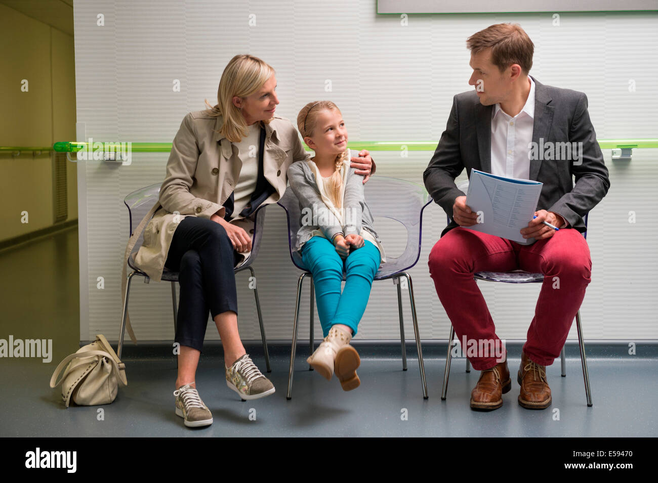 Couple with their daughter sitting in the waiting area of a hospital - Stock Image