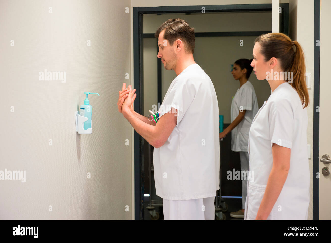 Male doctor using hygiene hand wash in hospital room - Stock Image