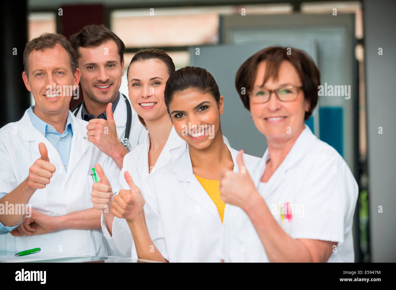 Portrait of medical-team showing thumbs up - Stock Image